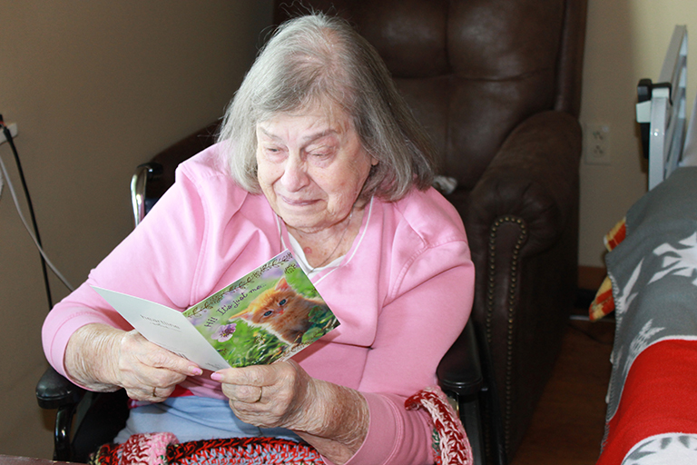 Resident Patricia White reading a card