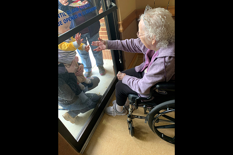 Gladys visiting with her great-grandson at the window