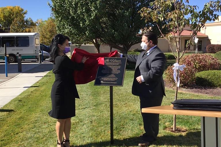 Juliana Martinez, admissions/marketing director, left, and Josh Martin unveil the memorial plaque.