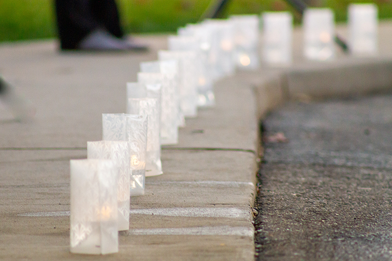 Luminaries line the sidewalk in honor of the 20 residents who passed away from COVID-19 at Rivergate Health Care Center.