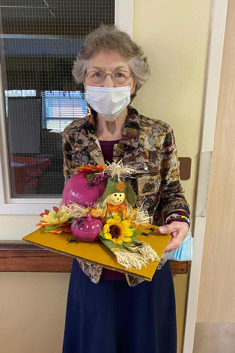Resident Linda Ogle with her winning pumpkin design at The Heritage Center