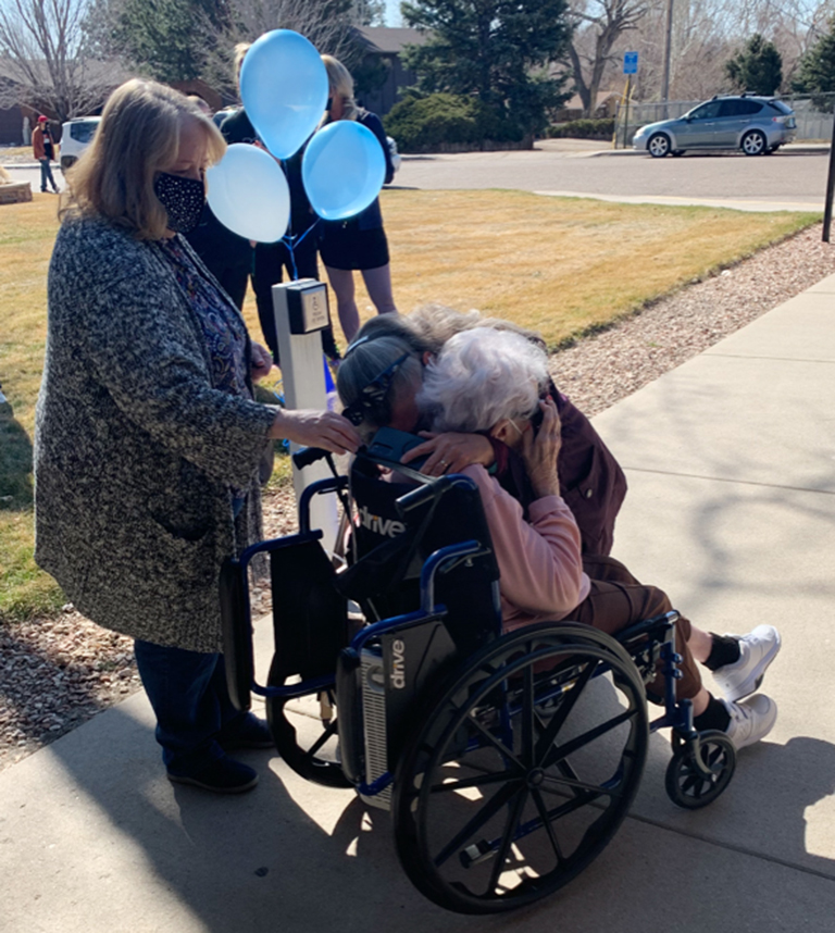 Resident Faye Cable hugs her daughter-in-law with her daughter, Gloria Webb, behind her.
